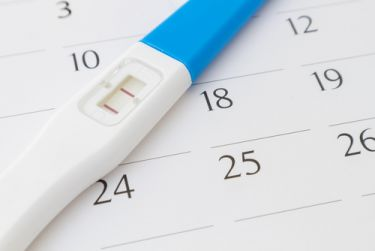 Checking pregnancy test against menstrual cycle on calendar