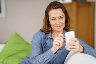 Woman looking up HRT alternatives on her phone