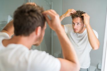 Man checking how thick his hair is