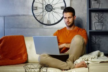 Man researching phimosis treatment on his laptop at home