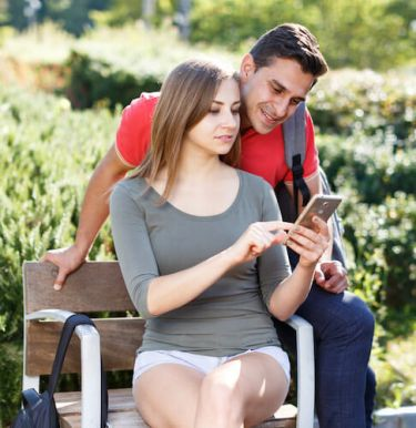 Couple looking up their contraceptive options on a smartphone on a park bench