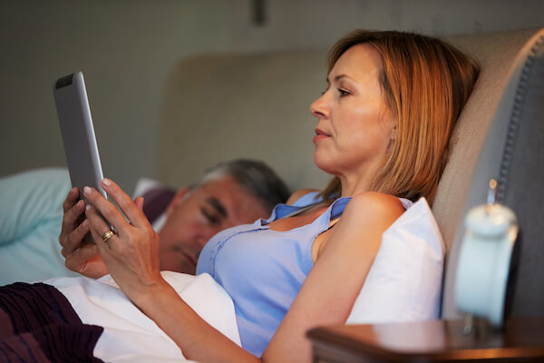 Woman researching bioidentical hormones on her tablet in bed